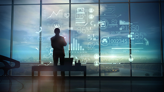 A silhouette of a man stands on the background of large office windows and views a hologram of corporate infographic with work data.