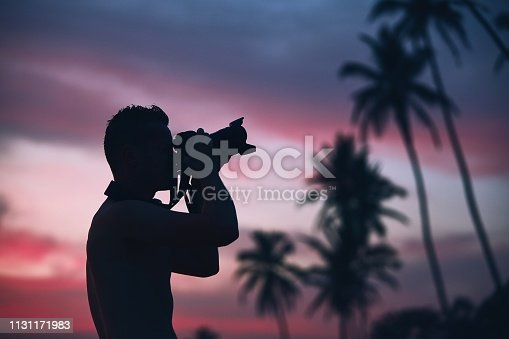 Silhouette of the young photographer with camera against palm tree at colorful sunset.