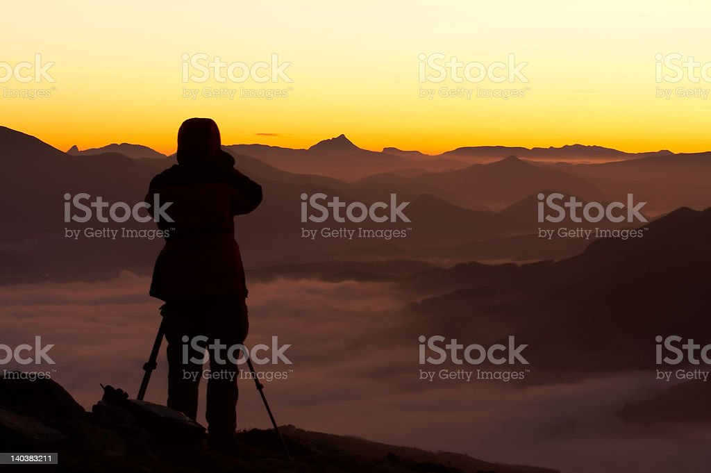 Silhouette of the photographer over a foggy mountain royalty-free stock photo