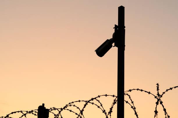 silhouette der überwachungskamera auf dem pol bei sonnenuntergang. beobachtung des umfangs des schutzgebietes mit stacheldraht. - revierverhalten stock-fotos und bilder