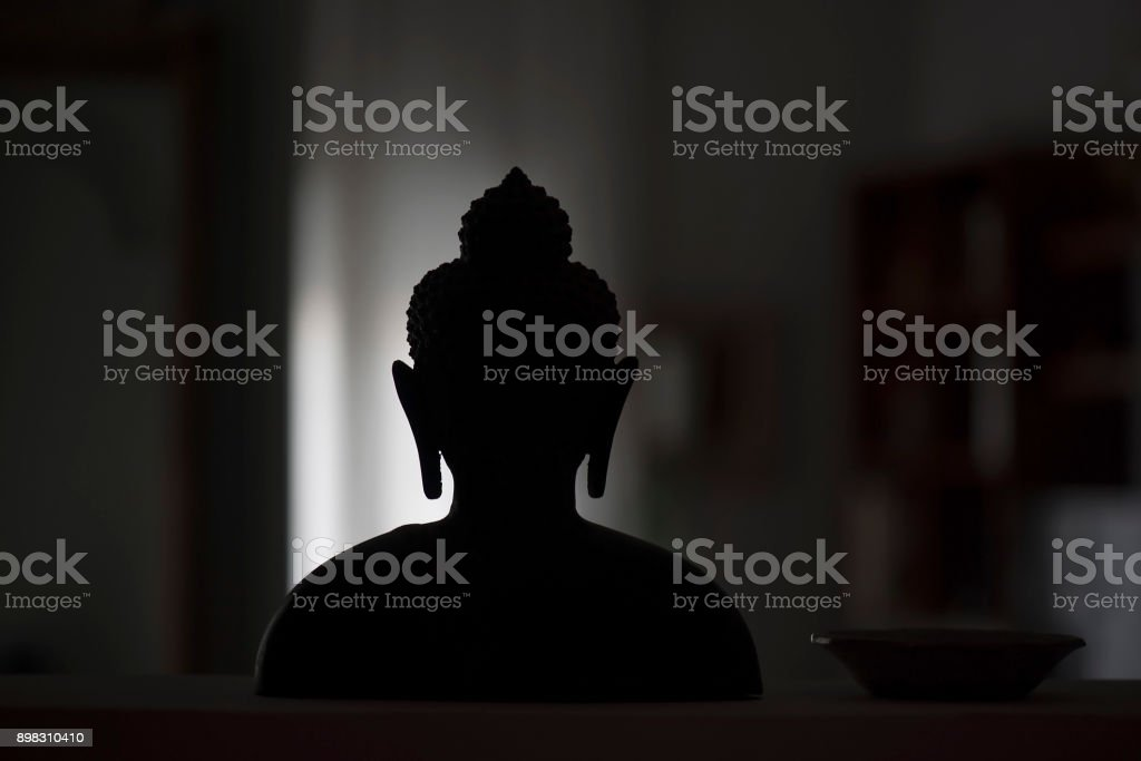 Silhouette of the statue of Buddha in a room, asian decoration, religion symbol stock photo