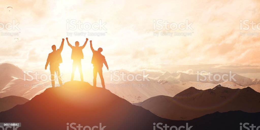 Silhouette of the team on the peak of mountain royalty-free stock photo