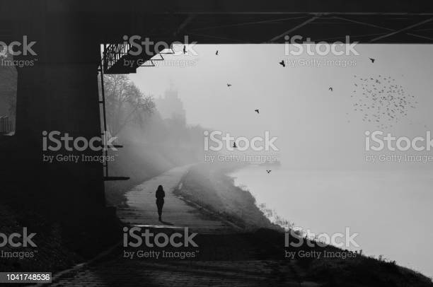 Photo of Silhouette of the woman under the bridge