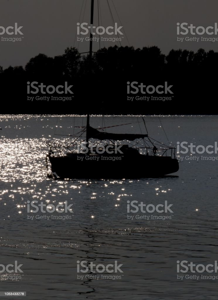 silhouette of the yacht on the lake stock photo
