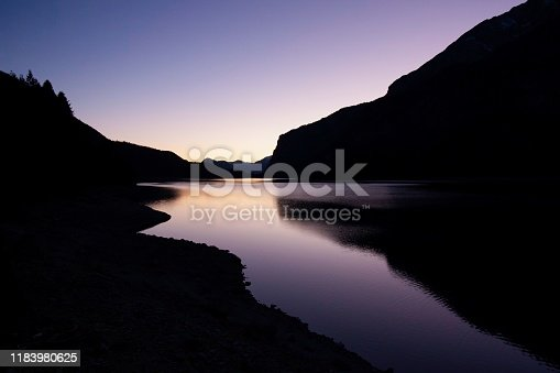 Black silhouette of the Dolomites mountains at sunset on Molveno lake (north Italy), purple, minimal, landscape.