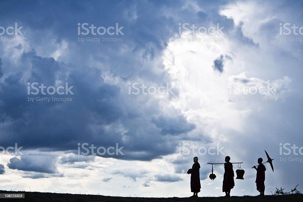 Silhouette of Three Buddhist monks stock photo