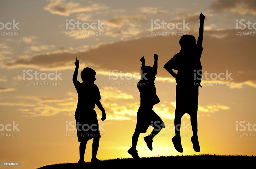 Silhouette of Three Children Jumping for Joy stock photo