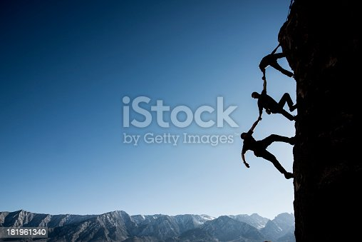 Silhouette of three climbers negotiating a vertical cliff face with a mountain ridge and blue sky in the background.  The climbers are holding hands and moving up the cliff, one behind the other.  The first climber is facing downwards, assisting the second and third climbers to ascend.