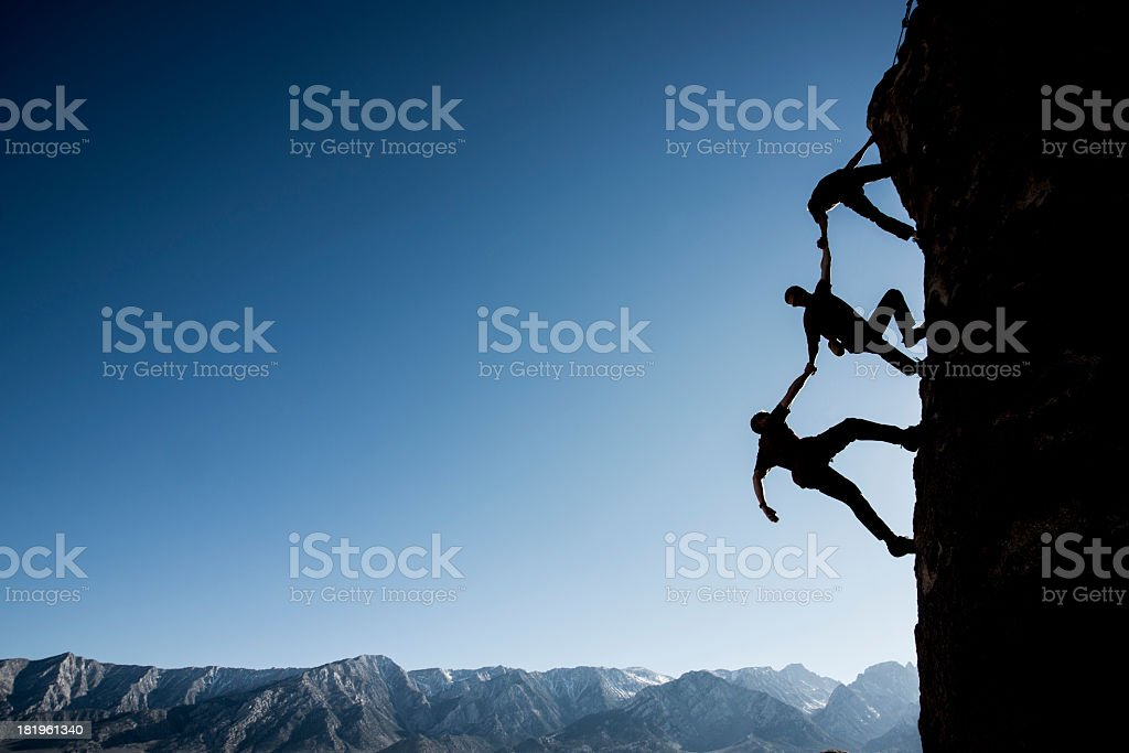 Silhouette of three climbers on side of a cliff stock photo