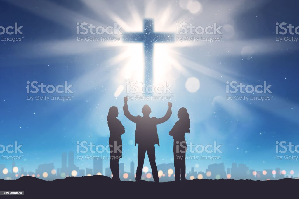Silhouette of three people looking christian cross on the sky stock photo