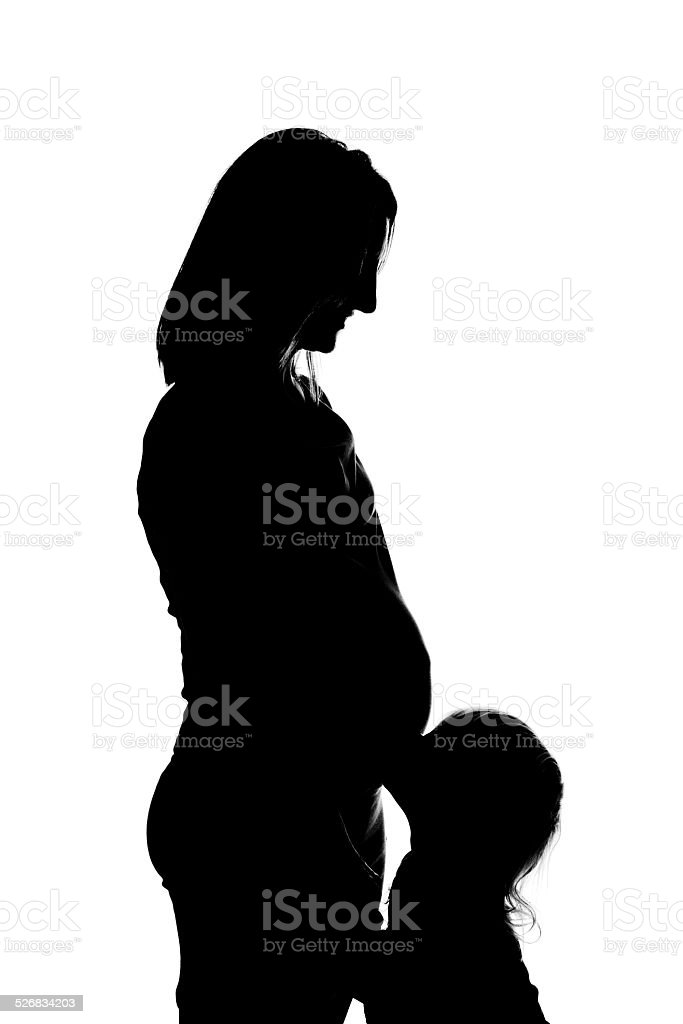 Silhouette Of Toddler Kissing Pregnant Mother's Belly stock photo