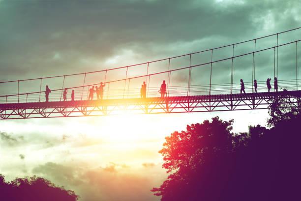 silhouette of tourist on suspension bridge walkway to the jungle in Surat Thani provine Thailand. stock photo