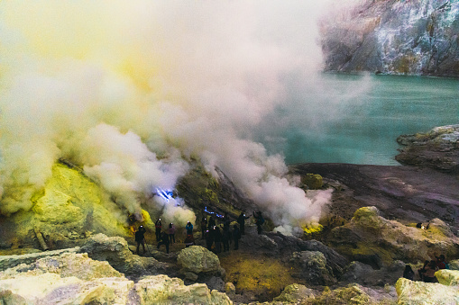 Tourists exploring the beautiful landscape of Ijen volcano and looking at the scenic blue fire and yellow sulfur smoke during sunrise on java island, Indonesia