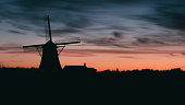 Silhouette of traditional Dutch windmill at sunset at sunset.