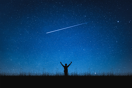 istock Silhouette of traveler standing on mountain and night sky with stars. Space background. 1077535240