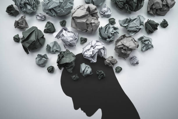 Silhouette of troubled person head. Concept image of anxiety and negative emotion. Waste paper and head silhouette. mental wellbeing stock pictures, royalty-free photos & images