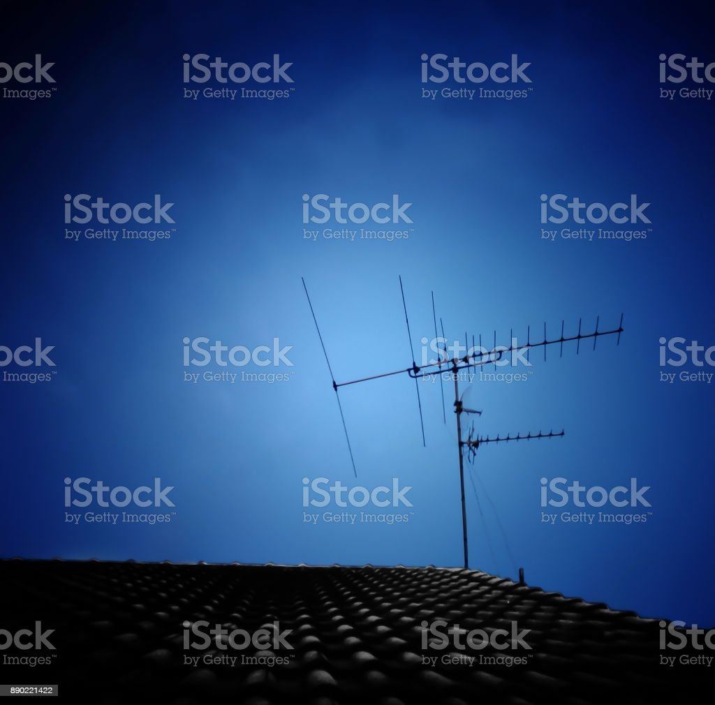 Silhouette of TV antenna installed on roof with dark blue sky background. stock photo