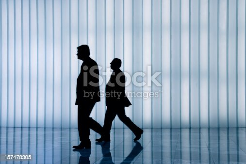 905689676 istock photo silhouette of two business men against curtain wall 157478305