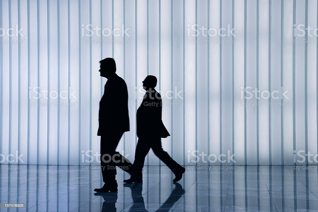 silhouette of two business men against curtain wall stock photo
