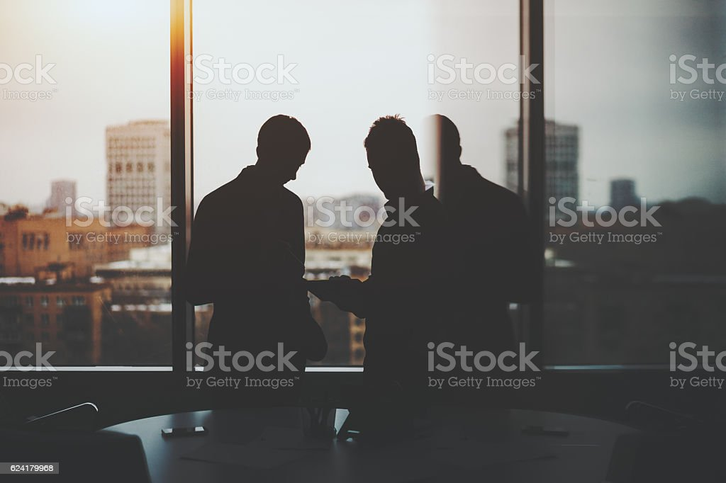 Silhouette of two businessmen in office interior ストックフォト