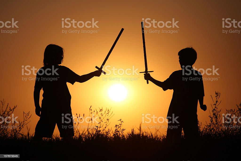 Silhouette of Two Children With Fantasy Swords royalty-free stock photo