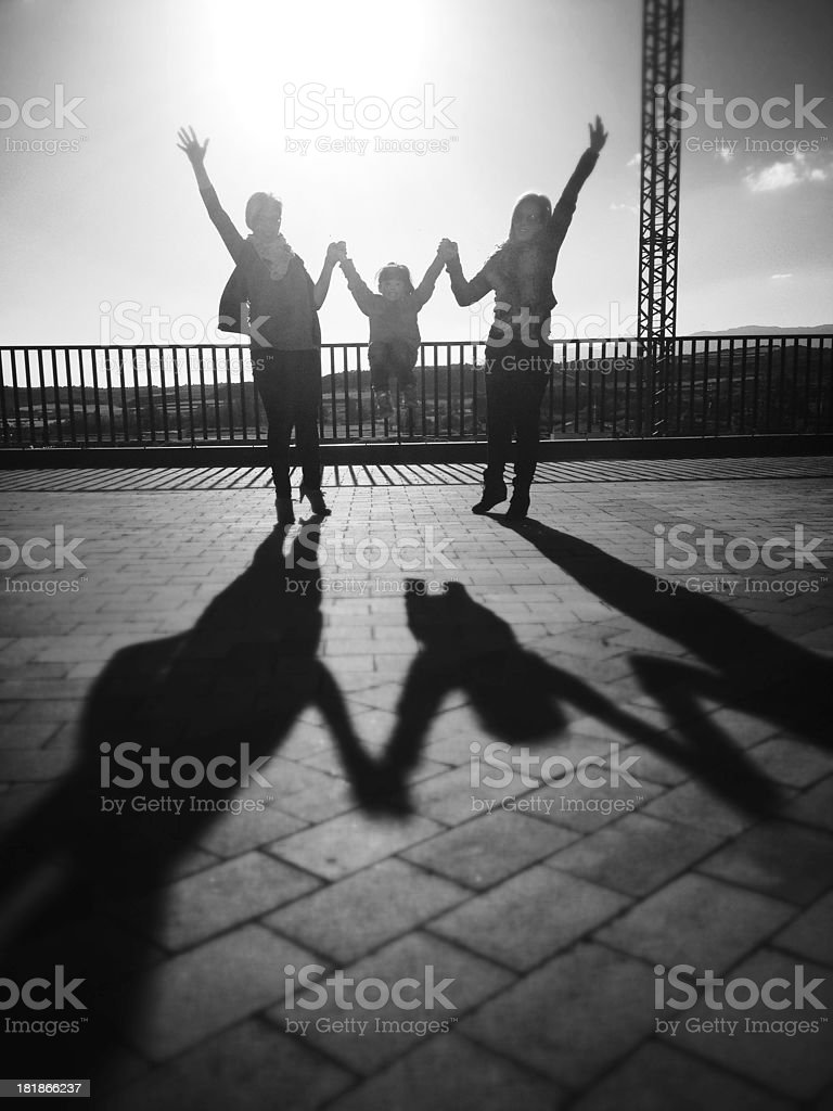 Silhouette Of Two Friends And A Child Jumping Stock Photo Download Image Now Istock