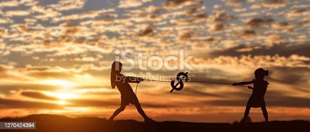 Silhouette of two girl pulling rope dollar at sunset background.