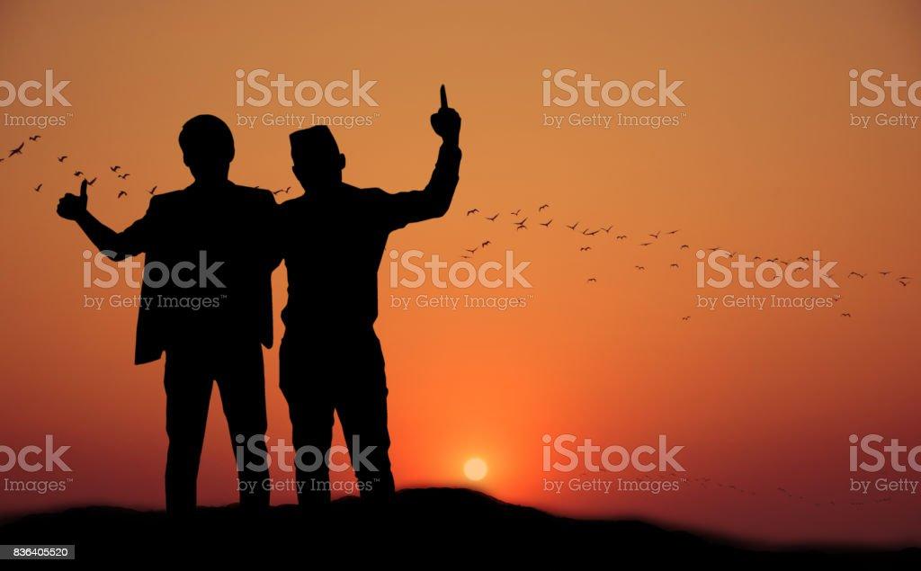 Silueta de dos personas felices al atardecer. concepto de éxito - foto de stock
