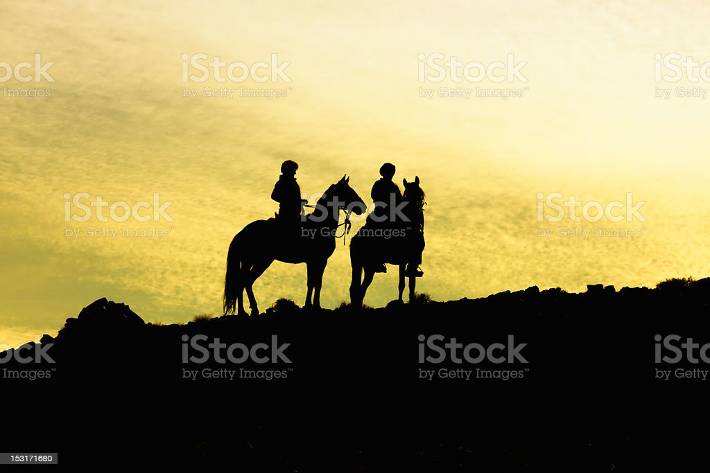Silhouette of two horses with riders stock photo
