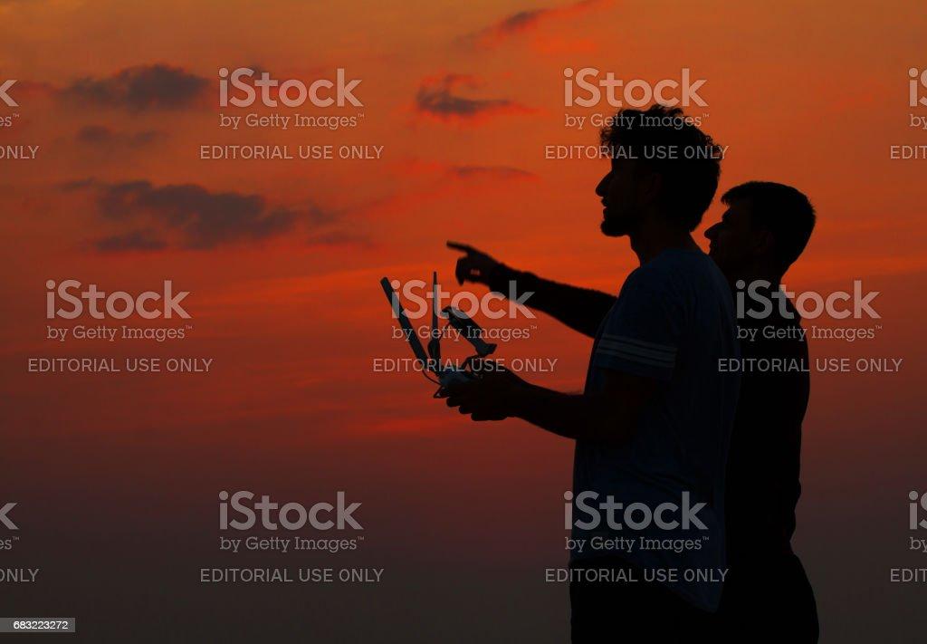Silhouette von zwei Mann Betrieb Drohne Lizenzfreies stock-foto