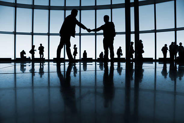 A silhouette of two men shaking hands in a business setting stock photo