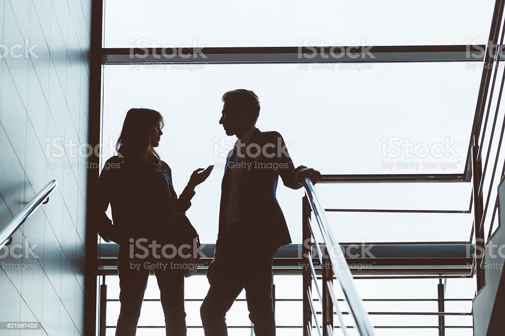 Silhouette of two people talking on steps stock photo