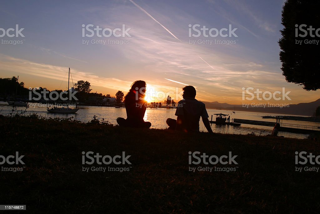 Silhouette of two people watching the sunset stock photo