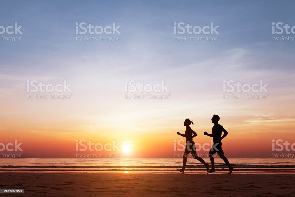 Silhouette of two runners running on the beach at sunset stock photo