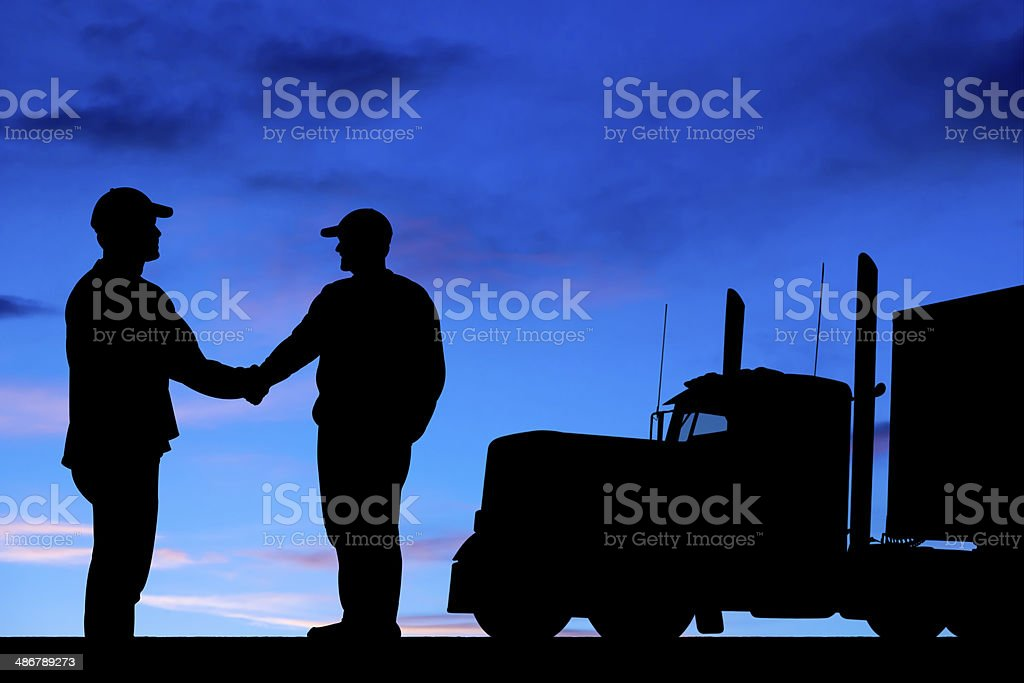 Silhouette of two truck drivers shaking hands stock photo