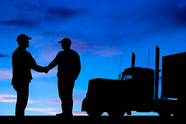 Silhouette von zwei LKW-Fahrer beim Händeschütteln – Foto