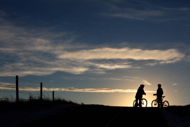 Silhouette of Two Unrecognizable People Biking on Bike Path stock photo