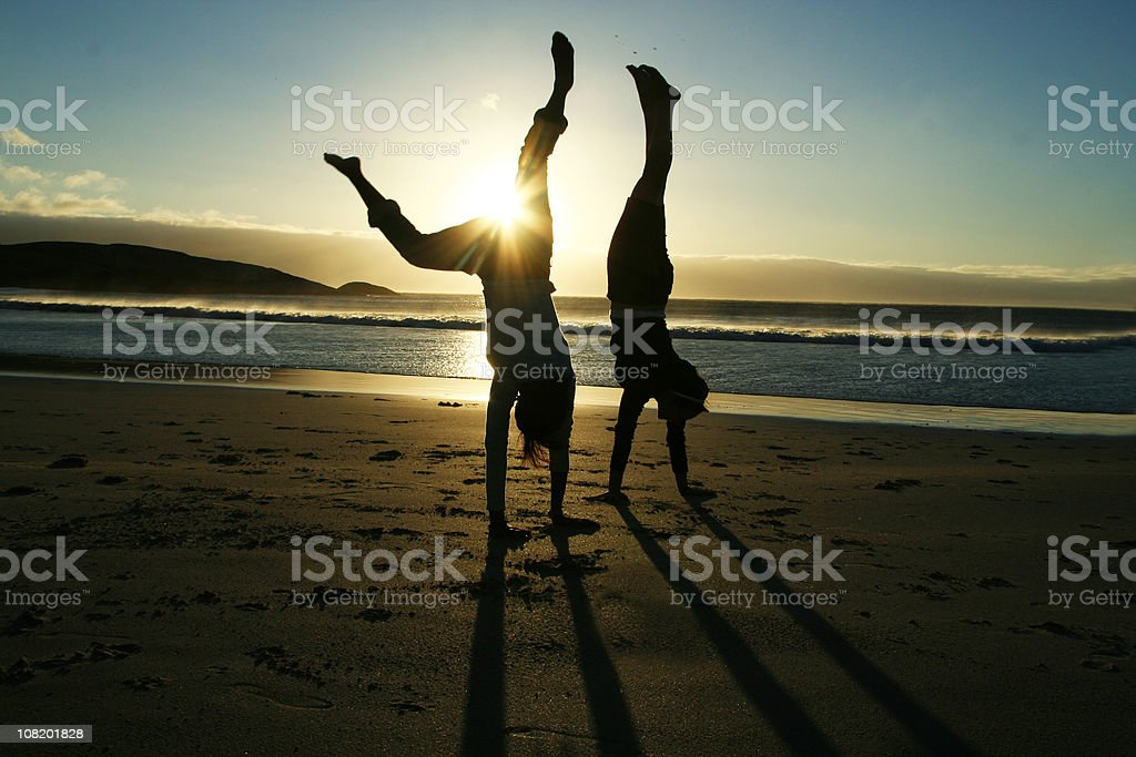 Silhouette of Two Women Doing Handstand on Beach at Sunset royalty-free stock photo