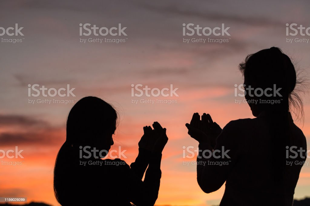 Silhouette Of Two Women Praying To God With The Bible Woman