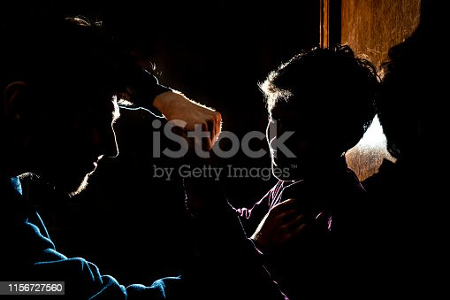istock silhouette of two young guys in the dark place bully and fight conception 1156727560