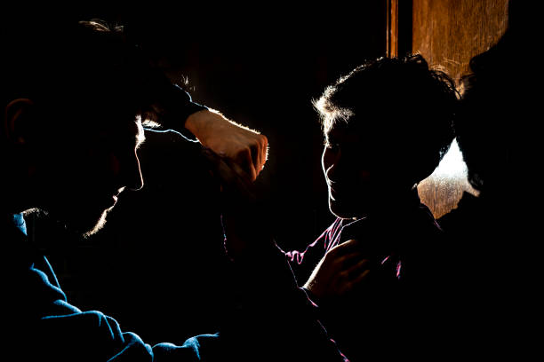 silhouette of two young guys in the dark place bully and fight conception stock photo