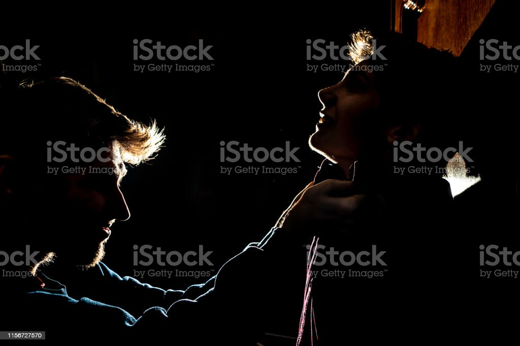 silhouette of two young guys in the dark place bully and fight concept