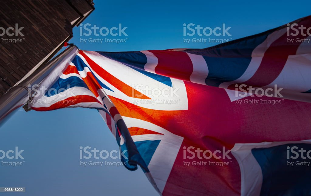 Silhouette of UK British Flag with blue Sky and Sun Waving Flag of the Great Britain - Royalty-free Awe Stock Photo