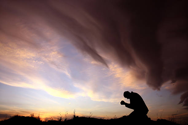 Silhouette of Unrecognizable Caucasian Man Praying During Storm stock photo