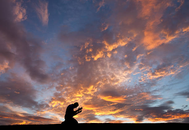 silhouette of unrecognizable male salvation prayer - god stock photos and pictures