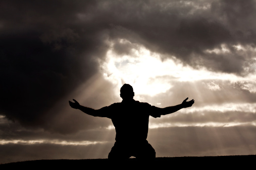 A man lifts his hand towards heaven. Silhouette, rear view, unrecognizable person. A man bowing down on his knees with his arms outstretched in praise and worship. Themes in the image include praise, worship, singing, voice, heaven, holy, righteous, sin, salvation, faith, healing, forgiveness, discipleship, godliness, god, easter, love, heart, wholeness, freedom, peace, and reverence. God beams are pouring down through the clouds adding plenty of atmosphere to the idyllic image.