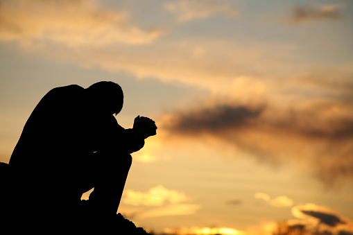 A silhouette of a man praying at sunset. Model is handsome Caucasian male in his 30s with unrecognizable side view. Model is folding his hands and bowing his head. Themes include meditation, spirituality, balance, freedom, vitality, hope, hurt, problems, addiction, struggle, anguish, help, god, healing, recovery, perseverance, coping, courage, strength, men, and asking for help.