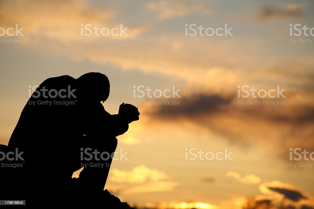 Silhouette of Unrecognizable Man Praying Outside stock photo