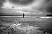 Silhouette of person standing head down on deserted beach in wintertime.