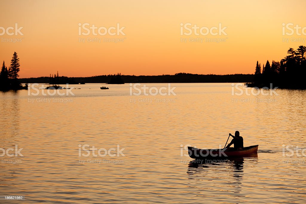 Silhouette of Unregonizable Male Canoeing on Beautiful Lake at Sunset stock photo